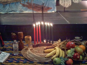 Kinara, Kikombe cha umoja y frutos en una mesa decorada para Kwanzaa. / Fotografía de Tiana Reid.-